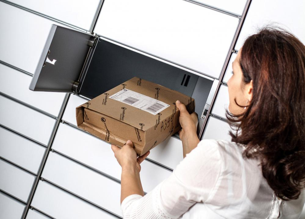 Woman receiving a parcel from a storage locker