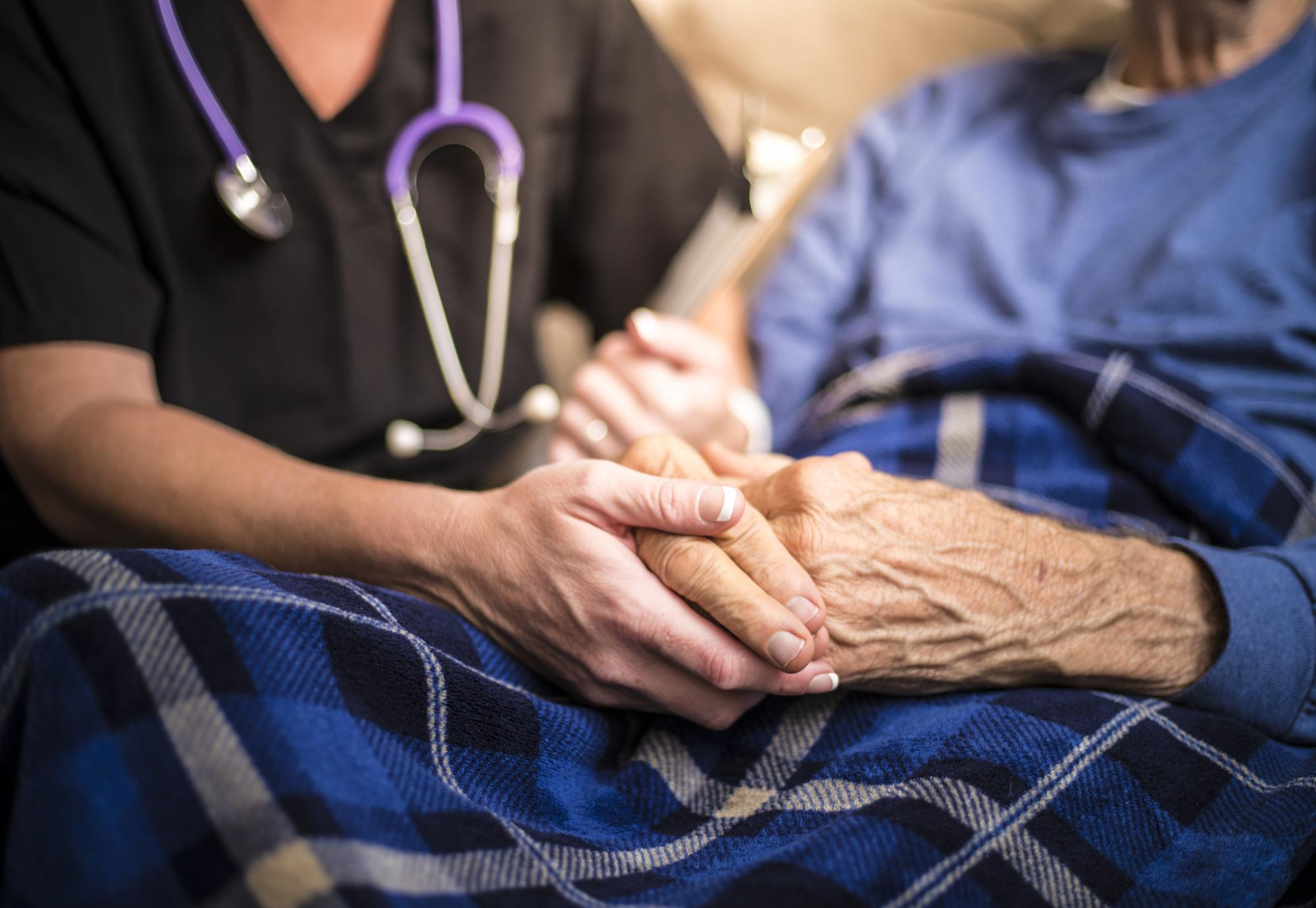 Nurse holding hand of elderly patient