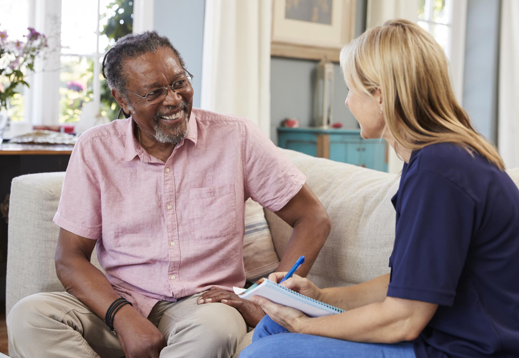 Female support worker talking with older male resident