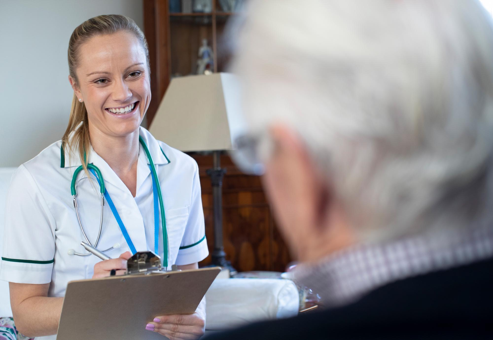 Female nurse recording information while interviewing a patient