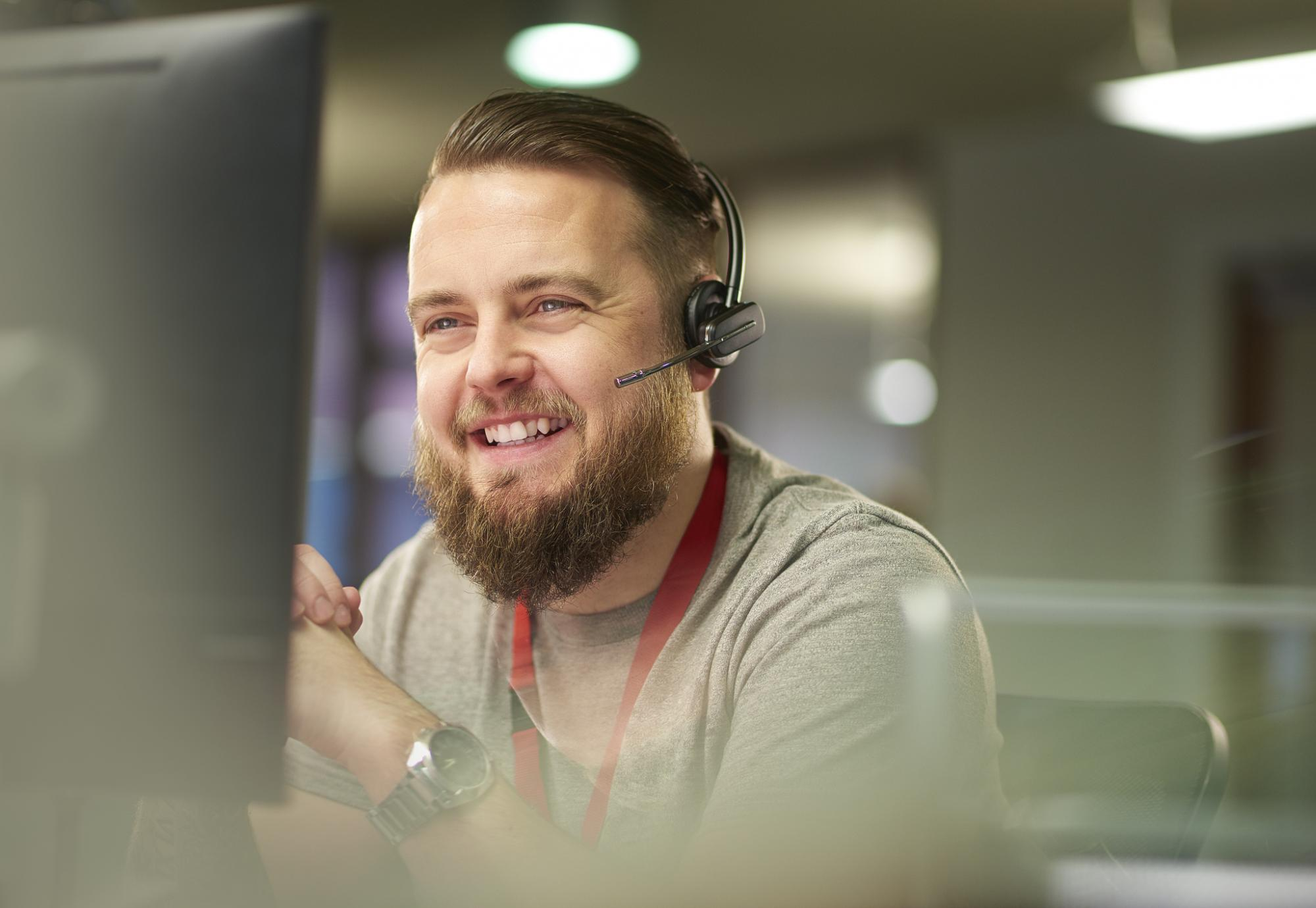 Smiling male call operator talking on a headset