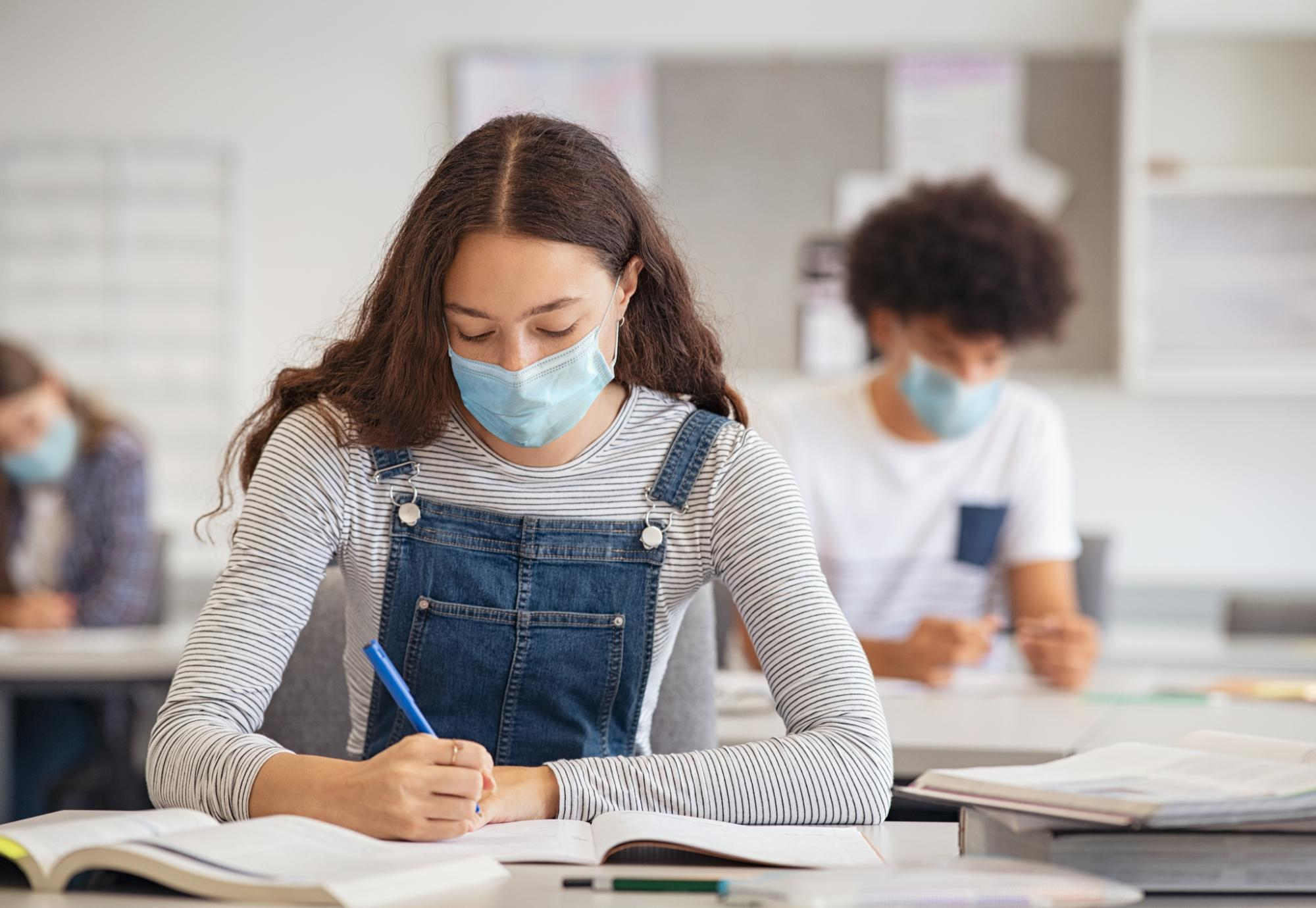 High school or college age girl in mask working at her desk
