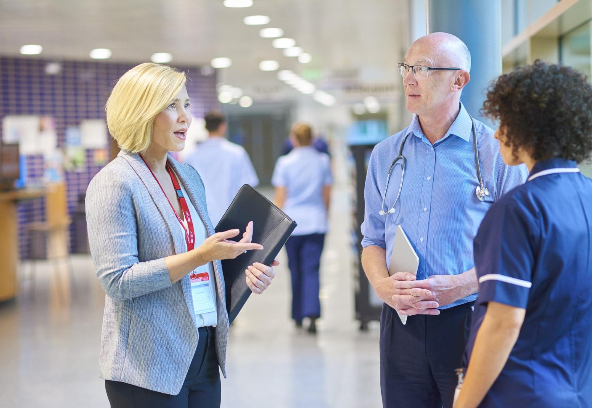 Hospital administrator in discussion with a doctor and nurse
