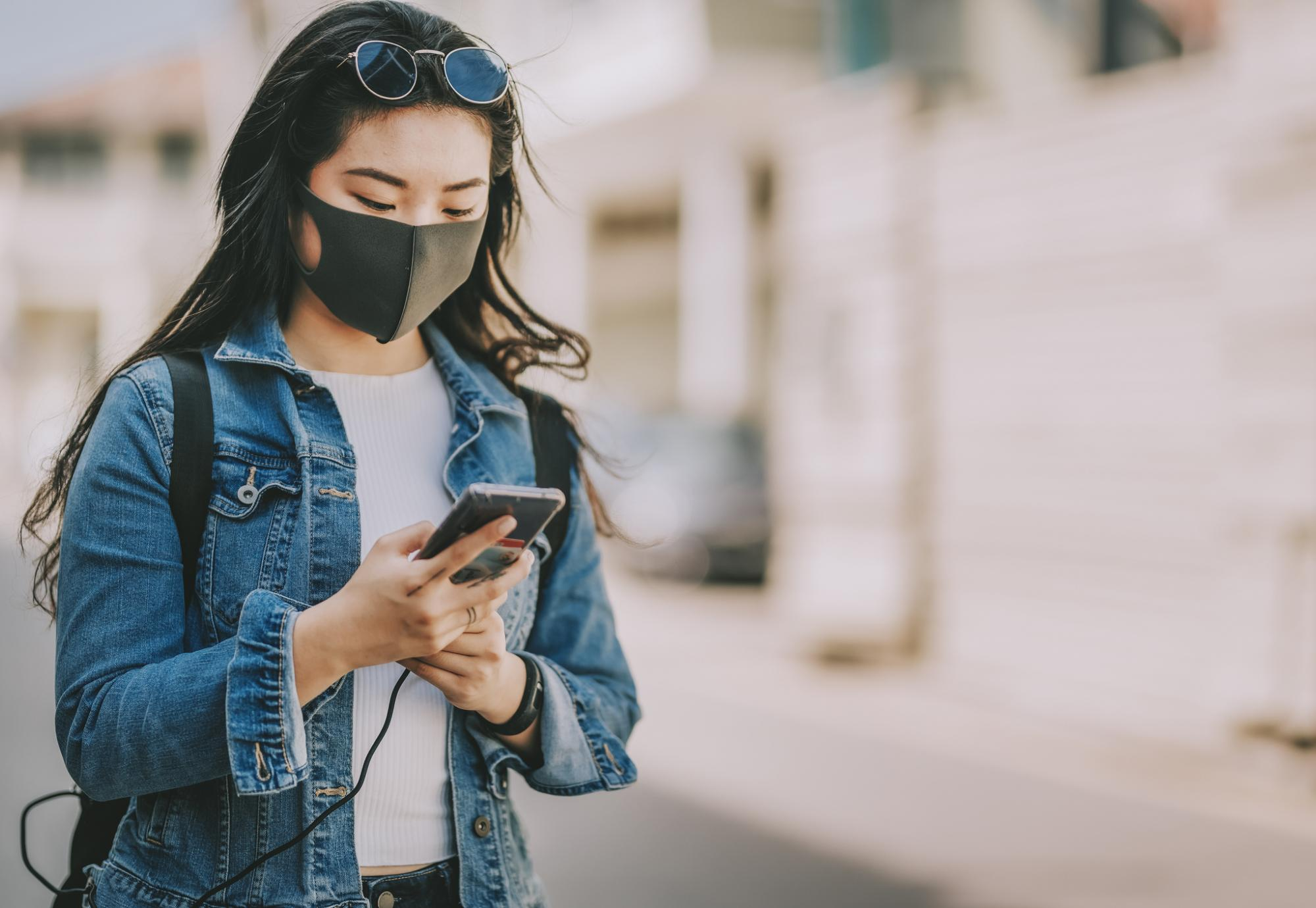 Young woman with a face mask using her phone