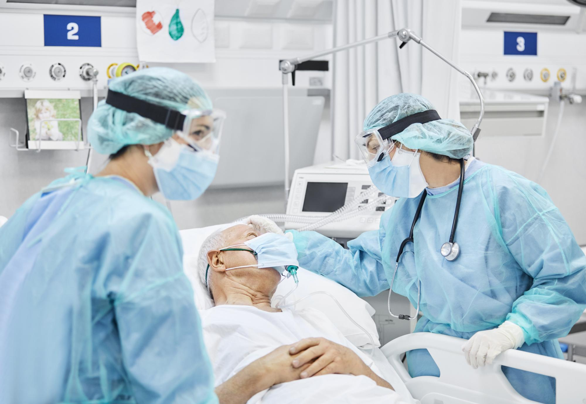 Medical professionals talking to a Covid patient