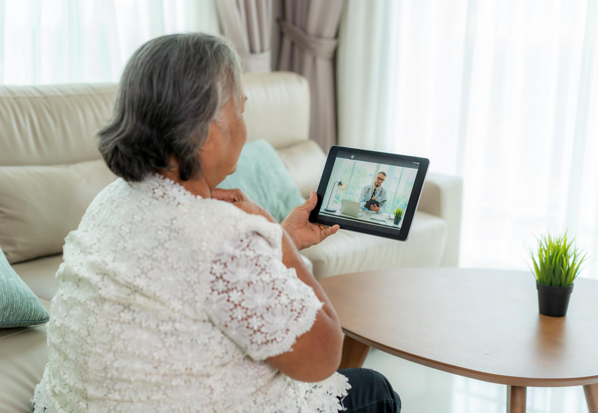Elderly woman in conversation with a doctor on a tablet PC