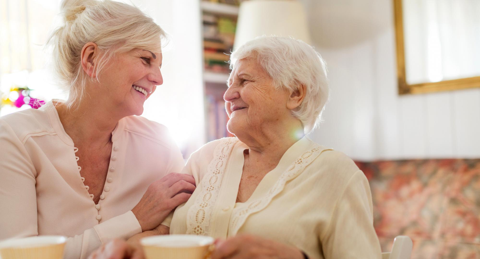 Woman supporting an elderly relative, in conversation
