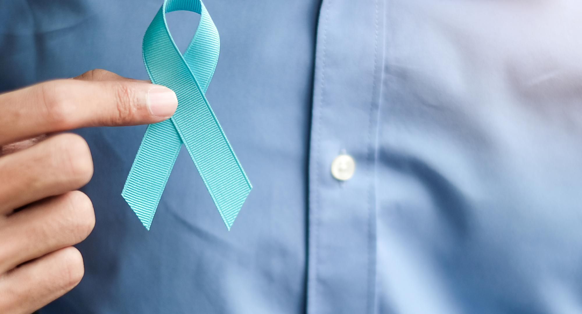Man holding a blue prostate cancer ribbon