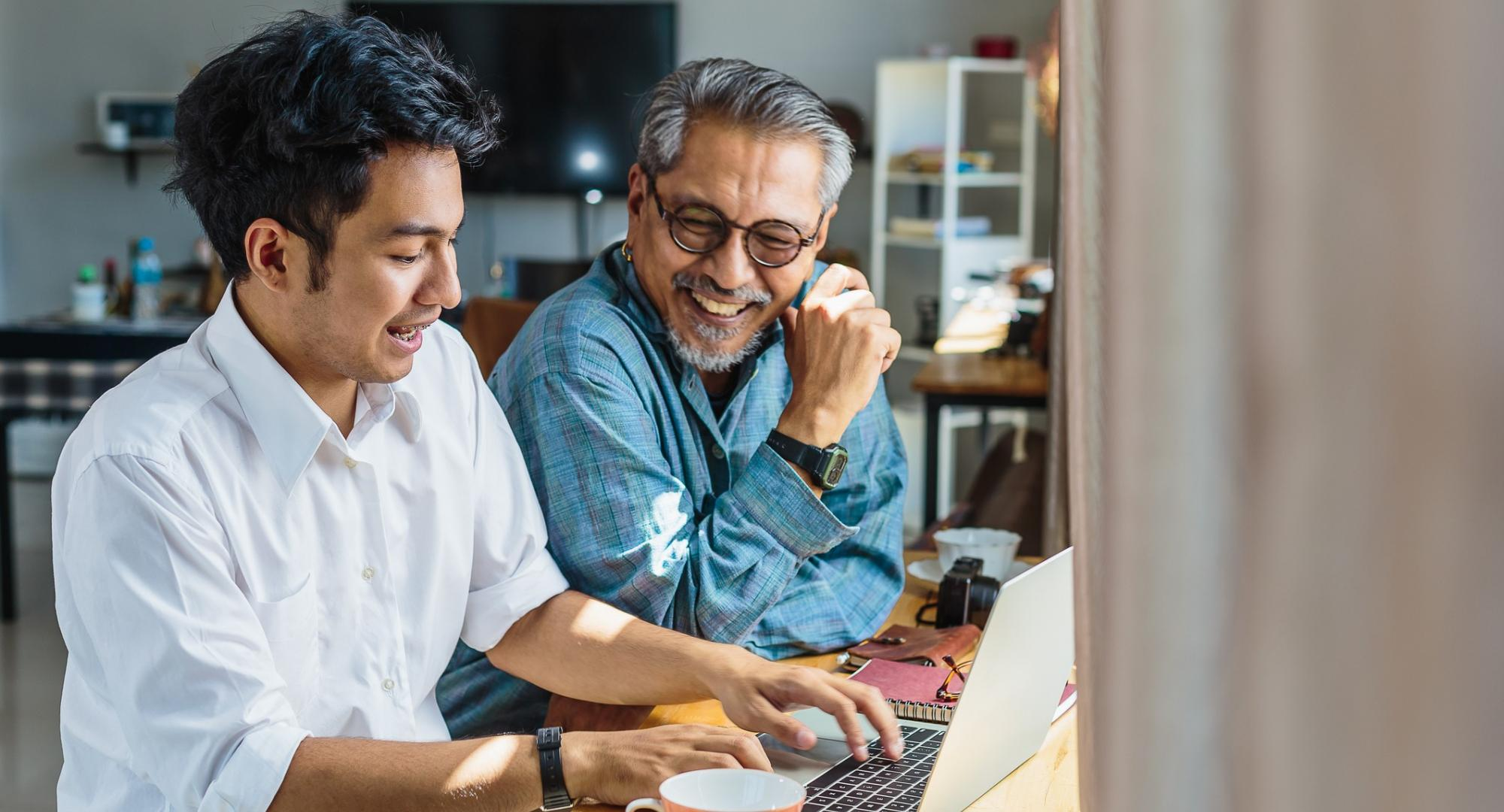 Asian father and son chatting at a laptop