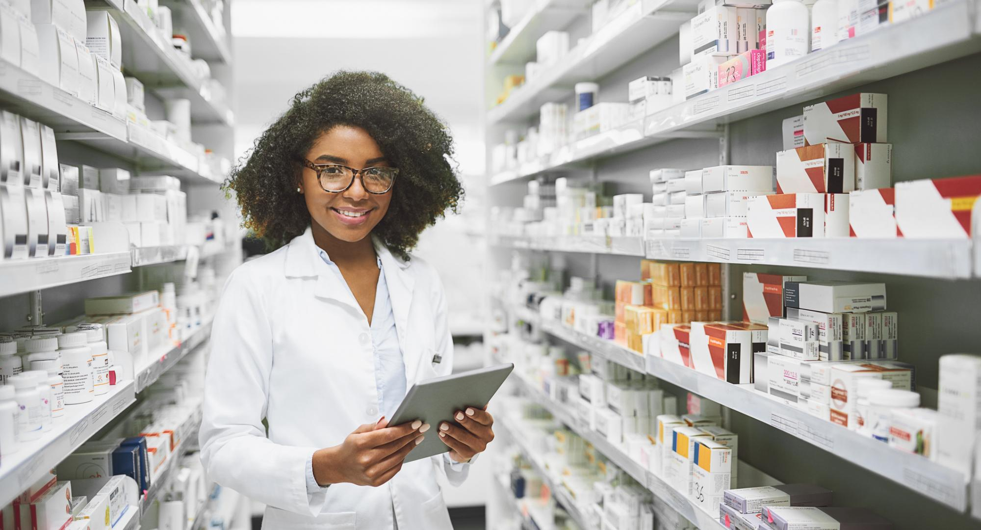 Young female pharmacist standing in an aisle of pharmaceuticals