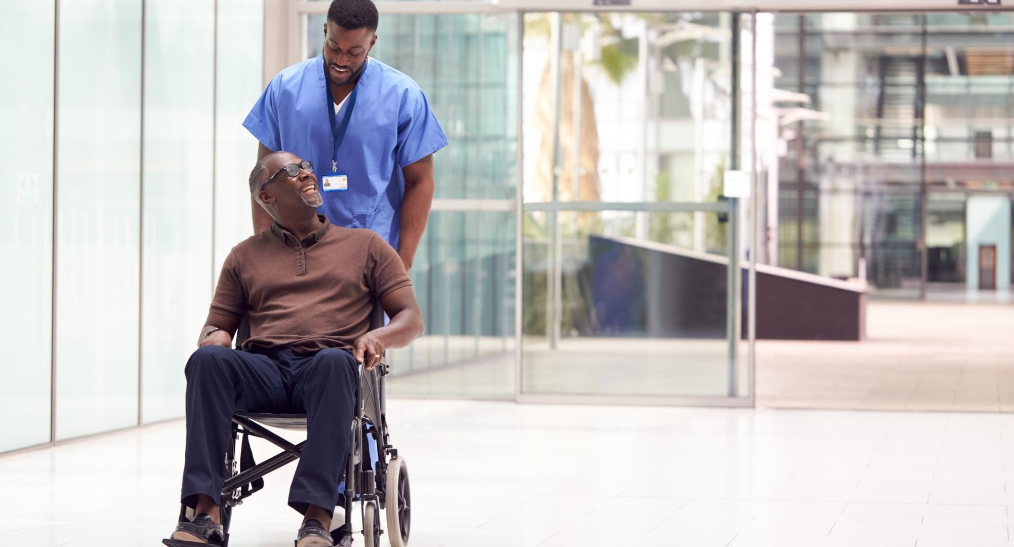 Porter pushing a patient through a hospital lobby