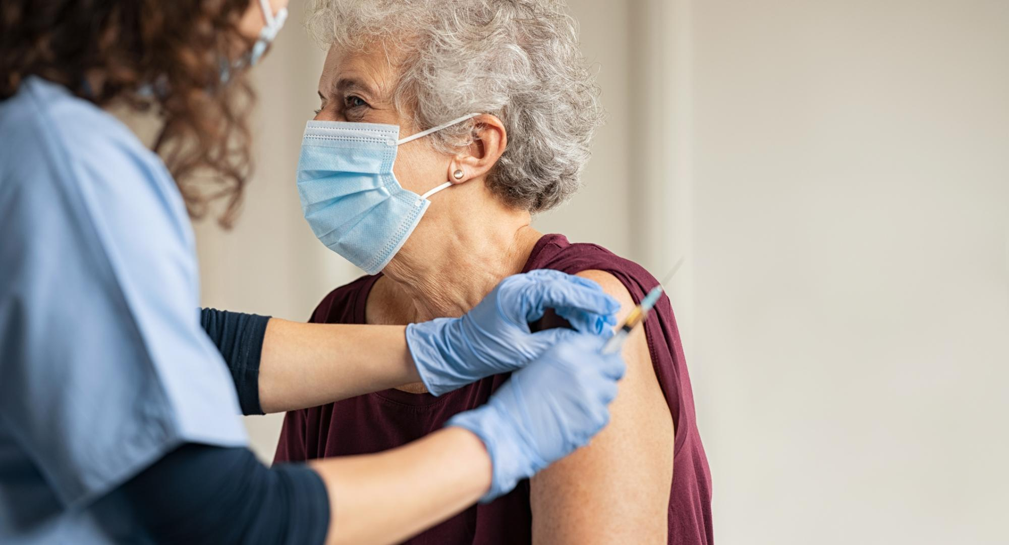 Elderly woman receiving a vaccine jab from a nurse