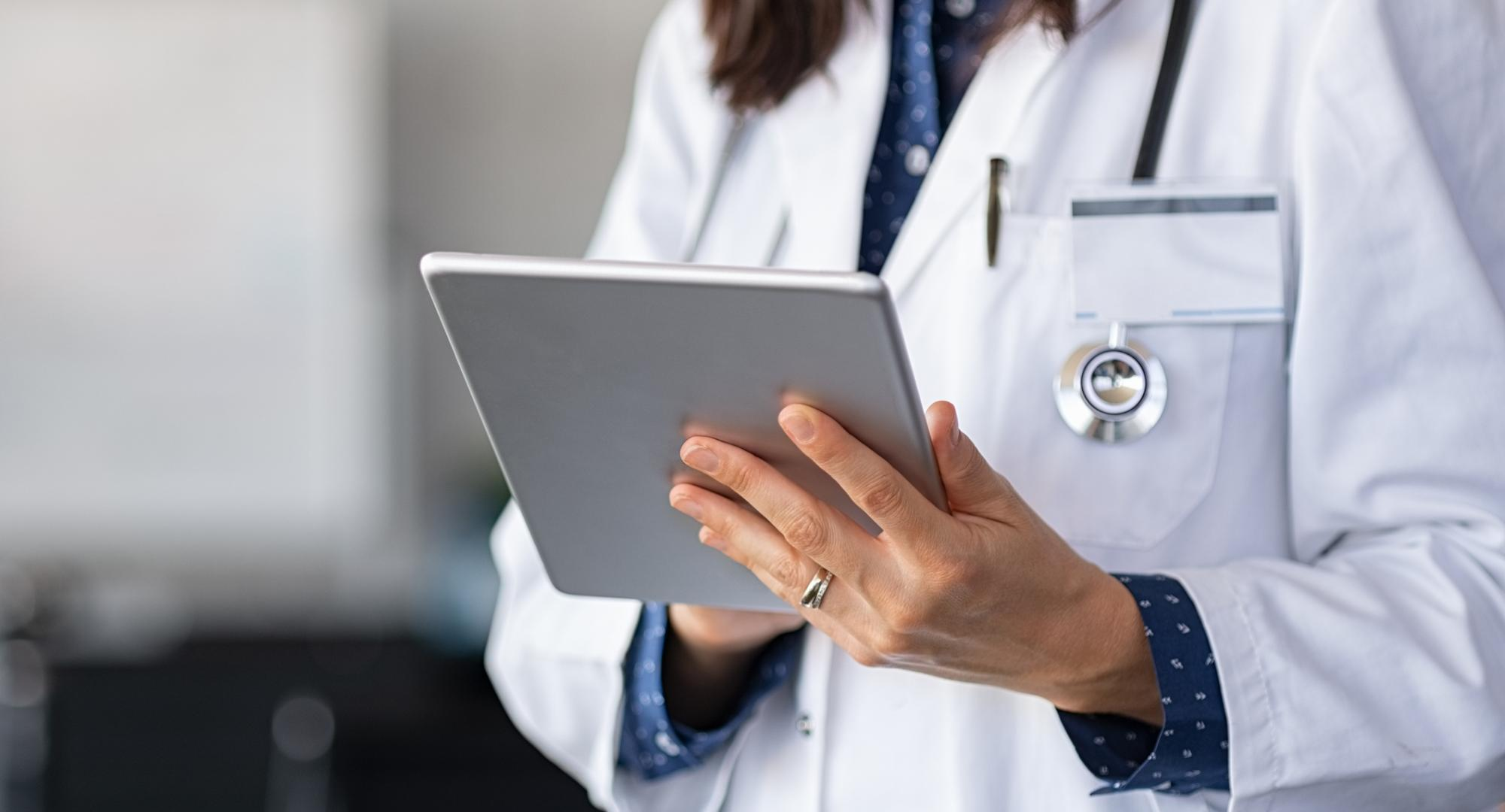 Doctor using a tablet PC to update records