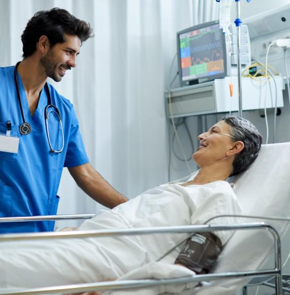 Male health professional at the bedside of a patient
