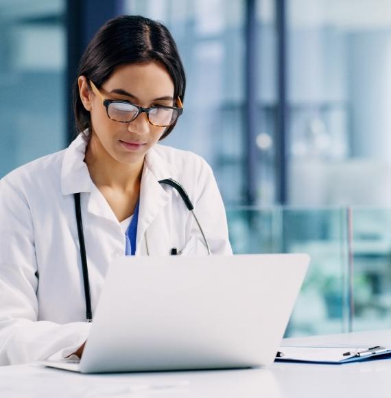 Female doctor looks at medical records on laptop.