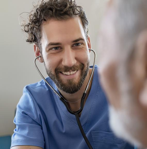 Male health professional listening to patient with stethoscope