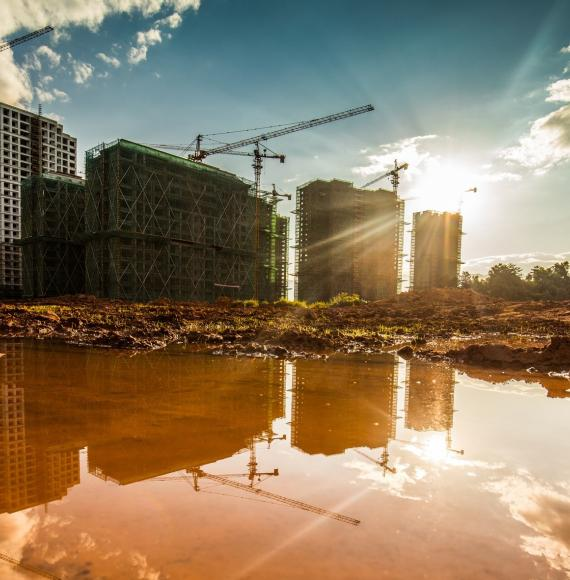 Construction site, with reflections off puddles on concrete in foreground