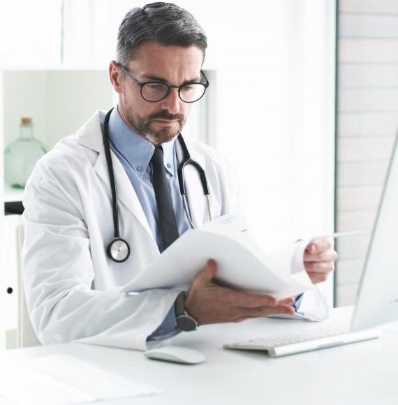 Male doctor reviewing paperwork at his desk