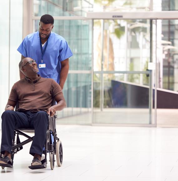 Male hospital porter transporting male patient in a wheelchair