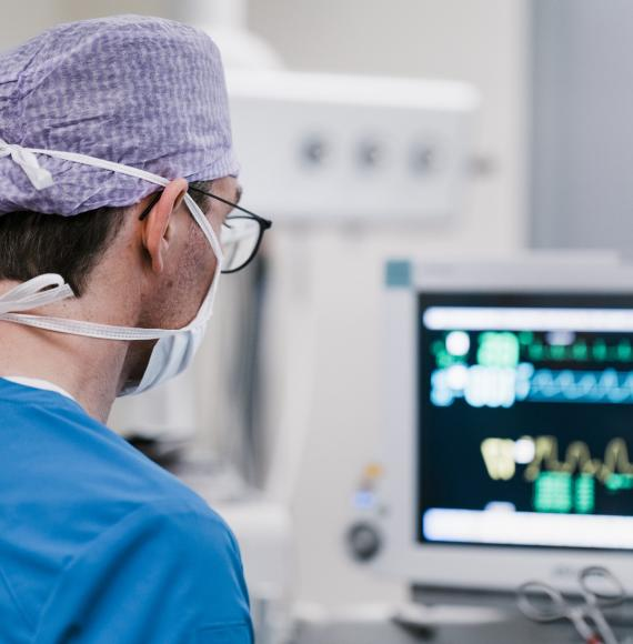 Male surgeon looking at a computer while in theatre