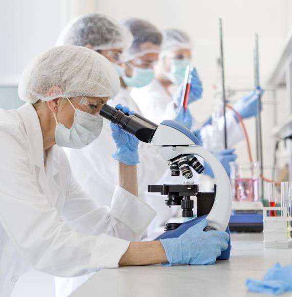 Lab technician looking into a microscope
