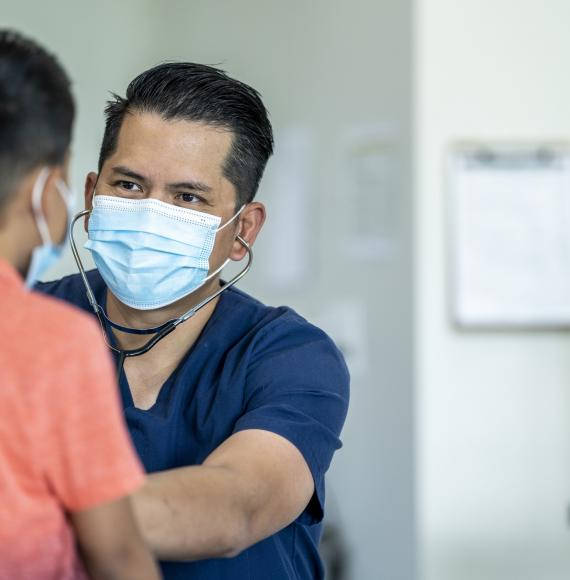 Male doctor examining a young patient