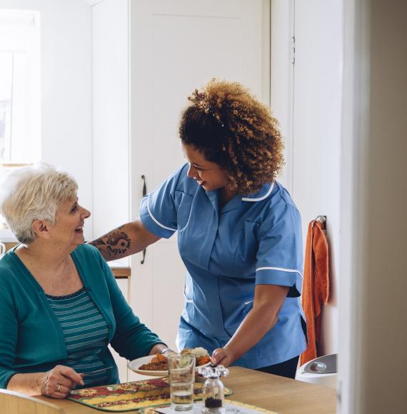 Social care professional supporting an elderly woman in her home