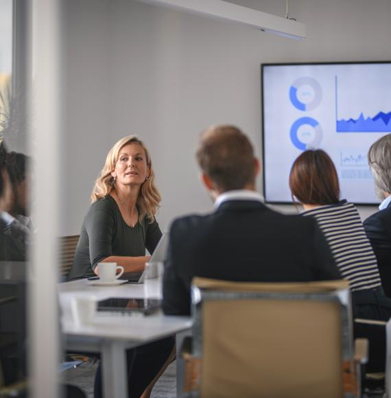 Female leader in conversation with colleagues during a board meeting