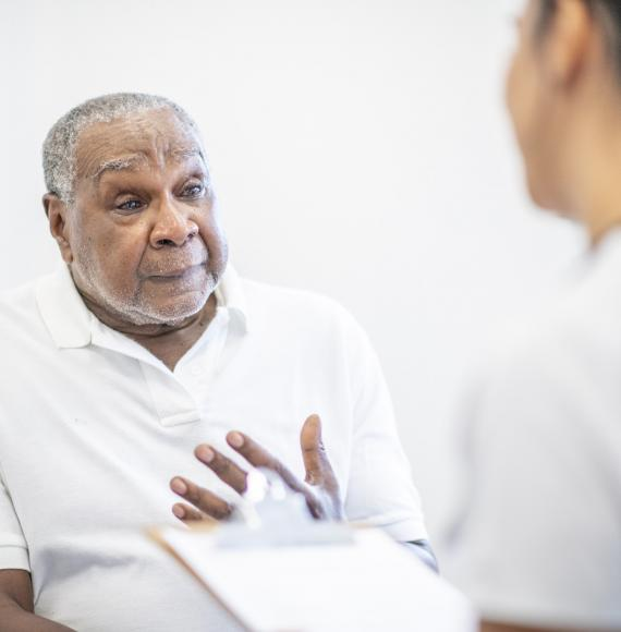 Elderly male patient discussing symptoms with a health professional
