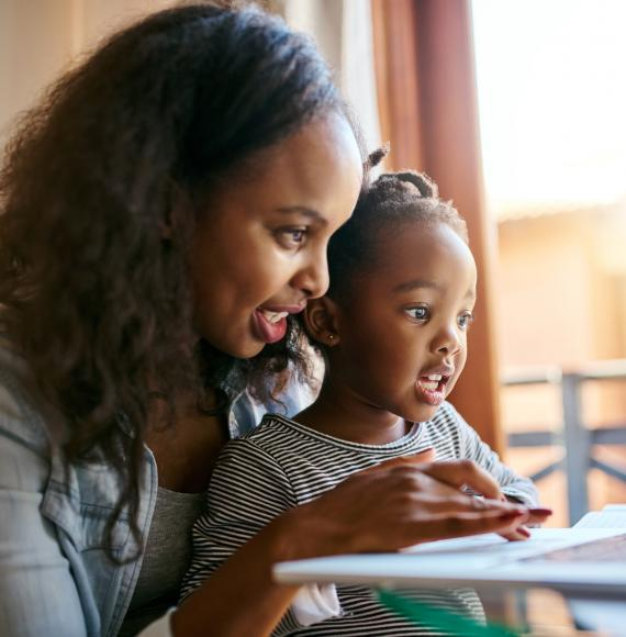 Young mother and her child looking at something on a laptop