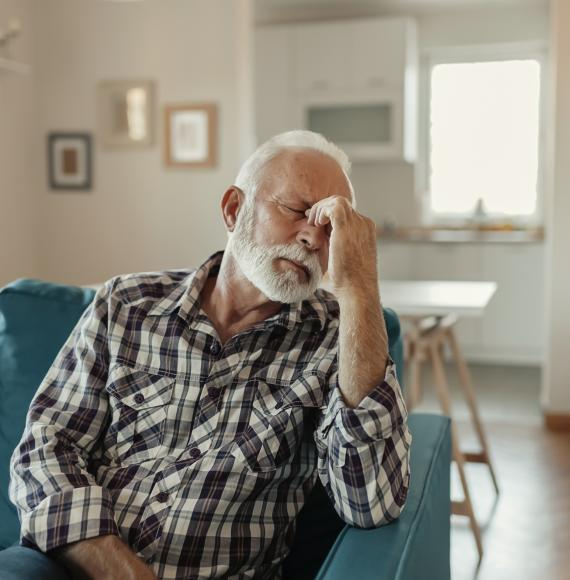 Older man holding his head with a migraine