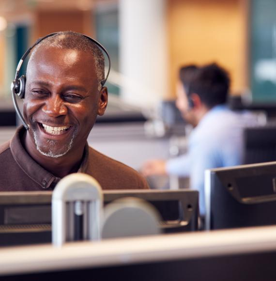 Smiling man operating a headset in a call centre environment
