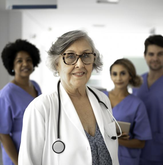 Retired doctor standing in front of younger health colleagues