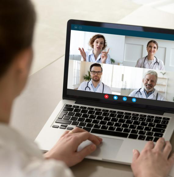 Doctor using a laptop to communicate virtually with colleagues
