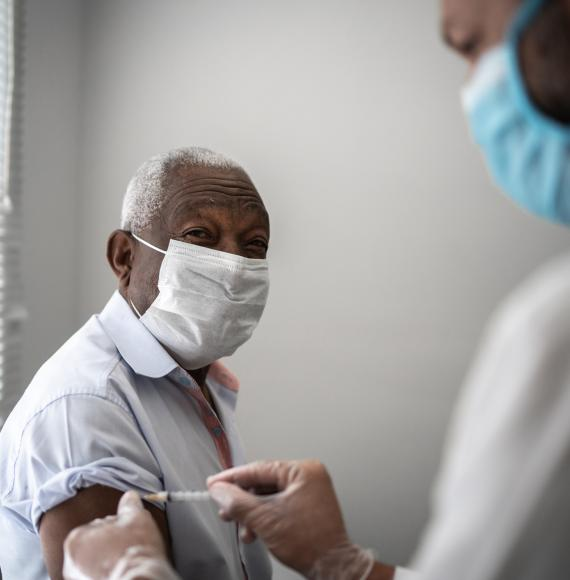Elderly man receives a vaccine jab