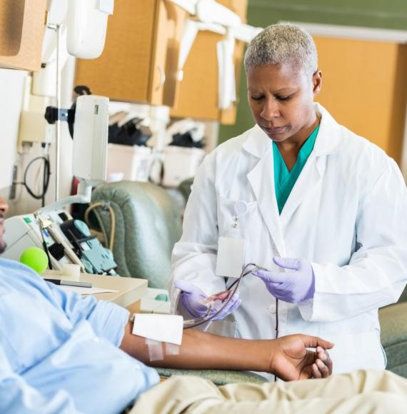 Male patient donating plasma with health professional observing