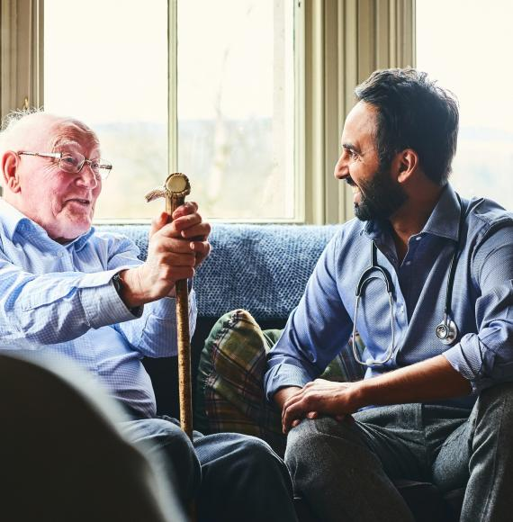 Elderly man with a cane talking with a male doctor