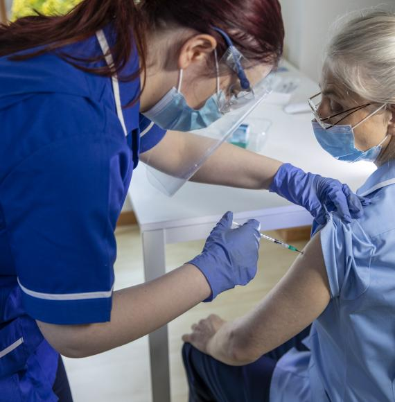 Nurse administering a vaccine jab to a colleague