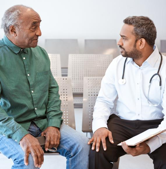 Man of South Asian descent talking with a doctor