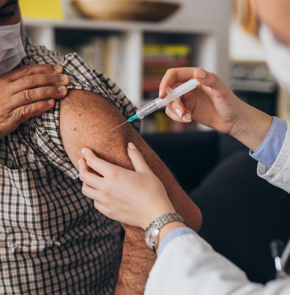 Elderly person receiving a vaccine jab