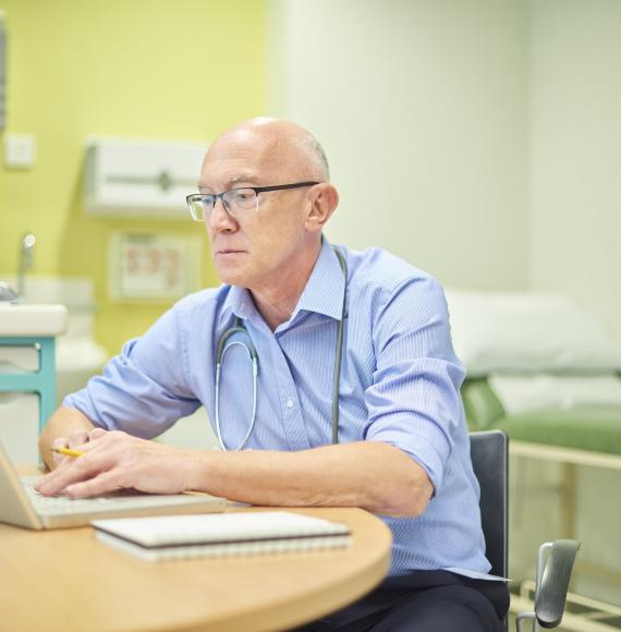Doctor using a laptop in his practice room